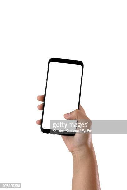 close-up of hand holding smart phone against white background - telephone stock pictures, royalty-free photos & images