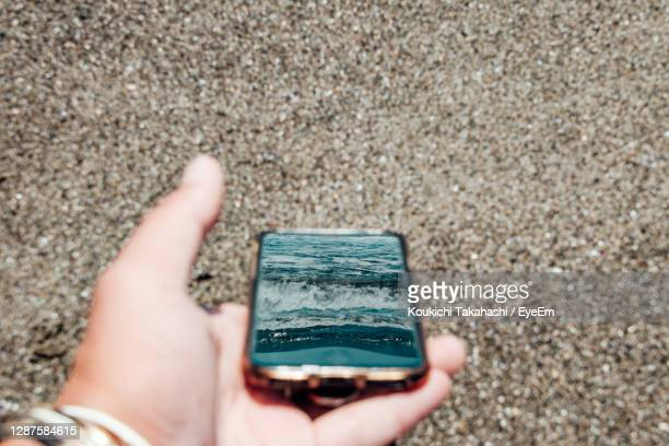 close-up of hand holding smart phone reflected sea against beach - koukichi stock pictures, royalty-free photos & images