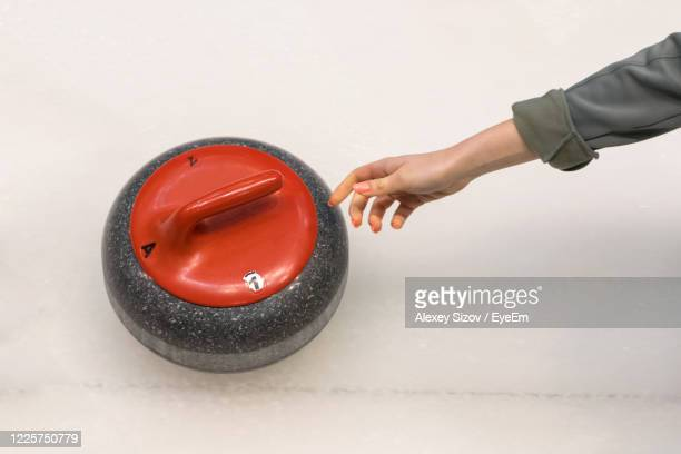 close-up of hand holding stone over white background - curling sport stock pictures, royalty-free photos & images
