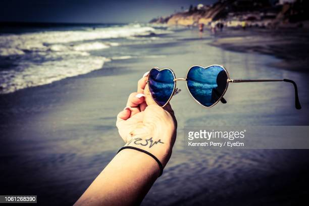 close-up of hand holding sunglasses against sea - tattoo designs hearts stock pictures, royalty-free photos & images