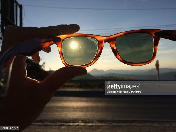 Close-Up Of Hand Holding Sunglasses Against Sky During Sunset