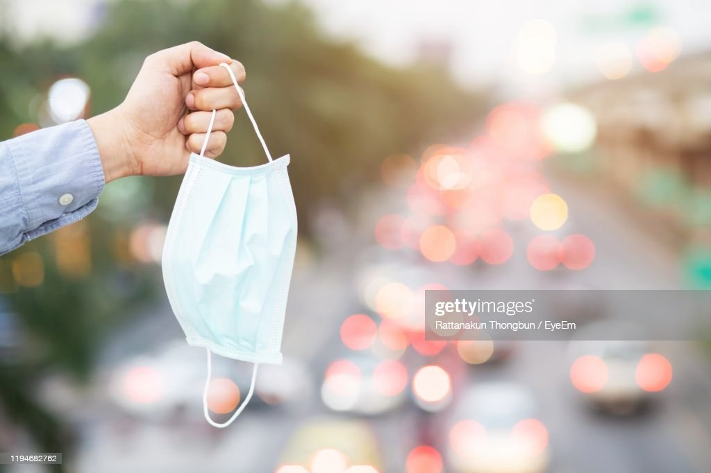Close-Up Of Hand Holding Surgical Mask : Stock Photo
