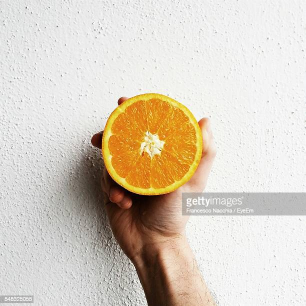 Close-Up Of Hand Holding Sweet Lime Slice Over White Background