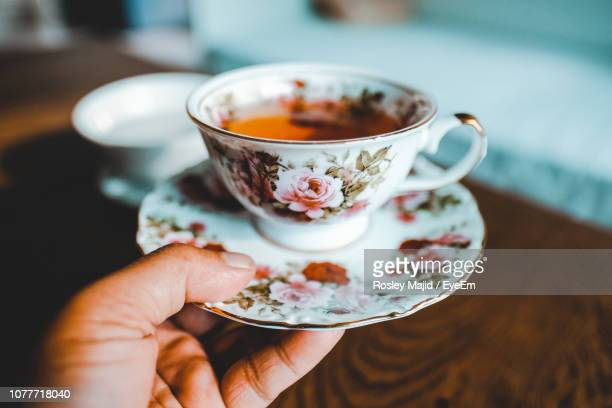 close-up of hand holding tea cup over table - saucer stock pictures, royalty-free photos & images