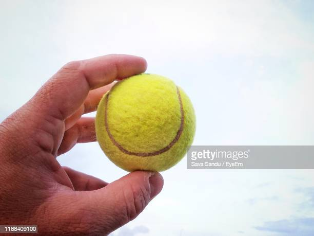 close-up of hand holding tennis ball against sky - tennis ball stock pictures, royalty-free photos & images