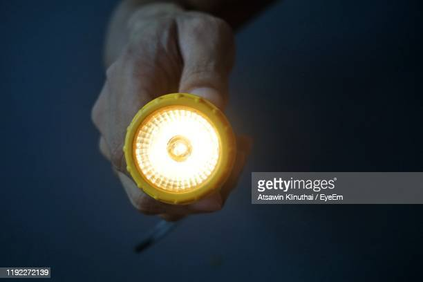 close-up of hand holding torch against black background - flashlight stock pictures, royalty-free photos & images