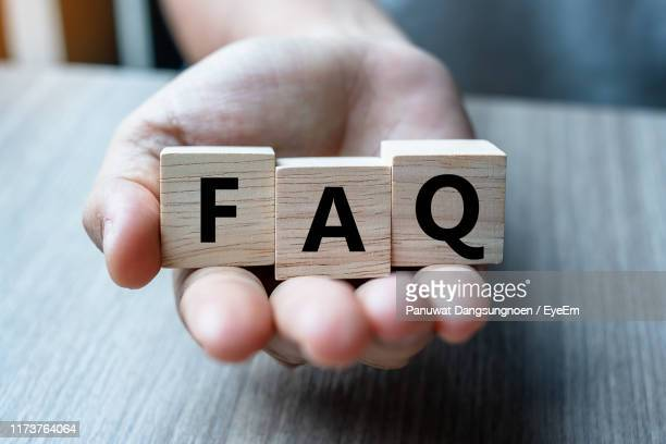 close-up of hand holding toy blocks with faq text on table - q and a stock pictures, royalty-free photos & images