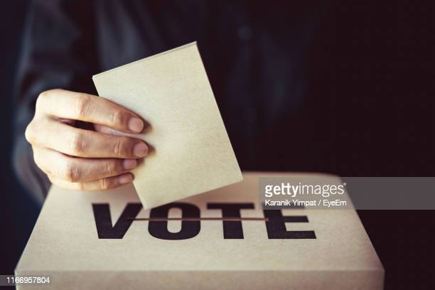 close-up of hand holding voting ballot - ballot box stock pictures, royalty-free photos & images