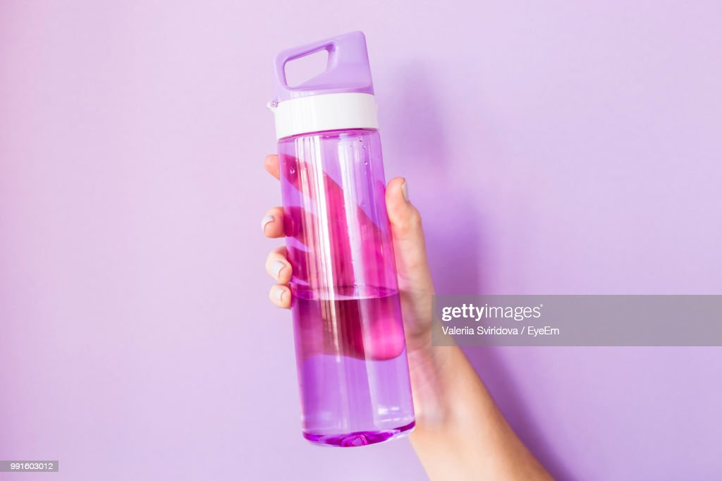 Close-Up Of Hand Holding Water Bottle Against Colored Background : Stock Photo