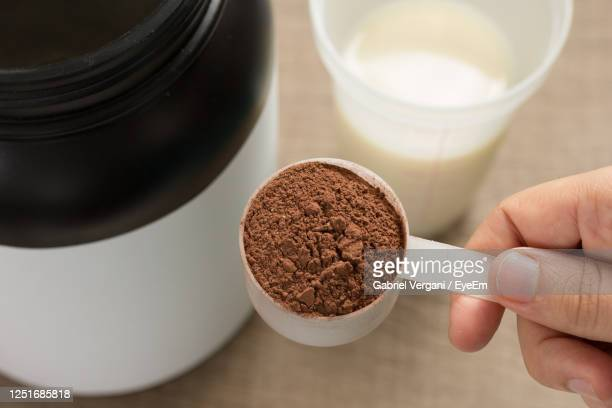 close-up of hand holding whey cup on table - protein drink stock pictures, royalty-free photos & images