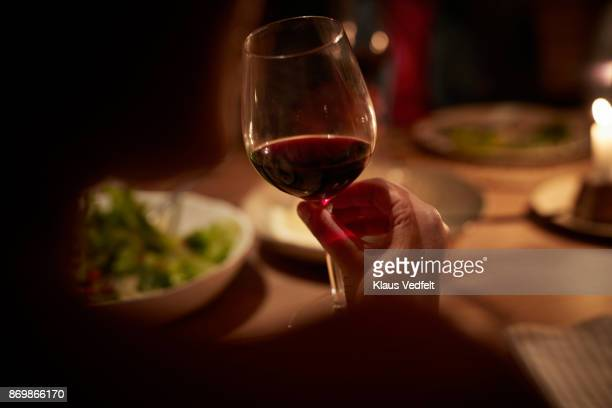 close-up of hand holding wine glass, at late dinner - wine glass stock photos and pictures