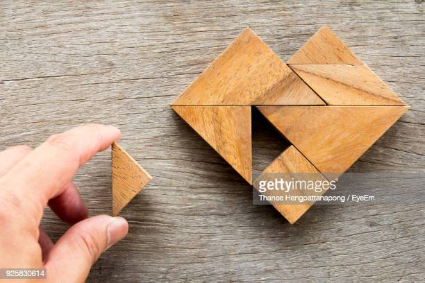 close-up of hand holding wooden toy blocks at table - raadsel stockfoto's en -beelden