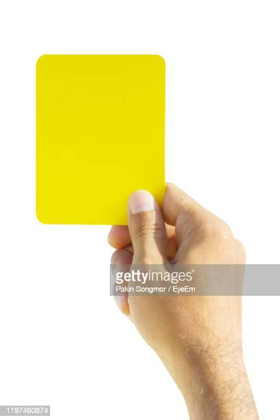 close-up of hand holding yellow card against white background - yellow card sport symbol stock pictures, royalty-free photos & images