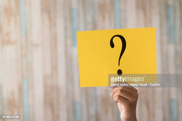 close-up of hand holding yellow paper with question mark - questions stock pictures, royalty-free photos & images