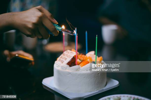 Close-Up Of Hand Lighting Birthday Candles