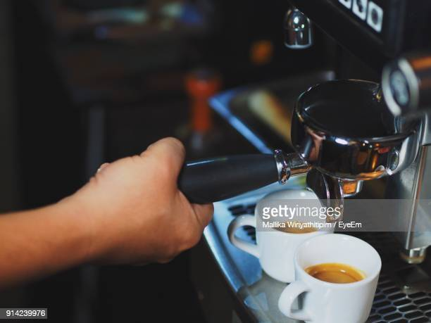 Close-Up Of Hand Making Coffee In Cafe