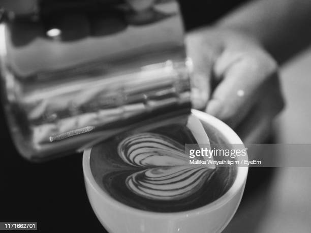 close-up of hand making froth art - black and white food stock pictures, royalty-free photos & images