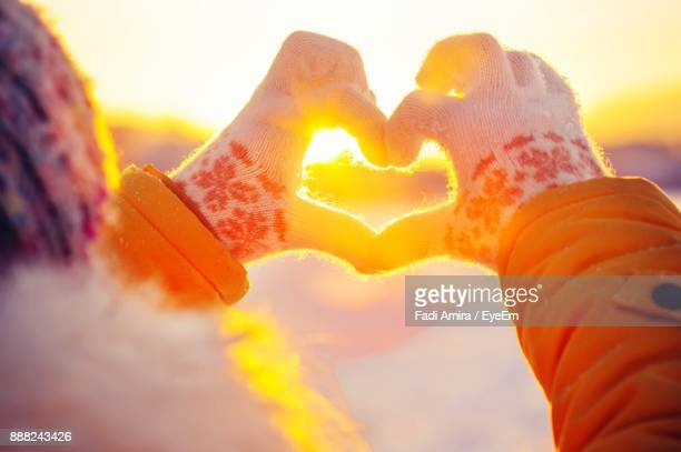 Close-Up Of Hand Making Heart Shape Against Orange Sky During Winter