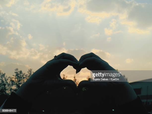 Close-Up Of Hand Making Heart Shape Against Sky During Sunset