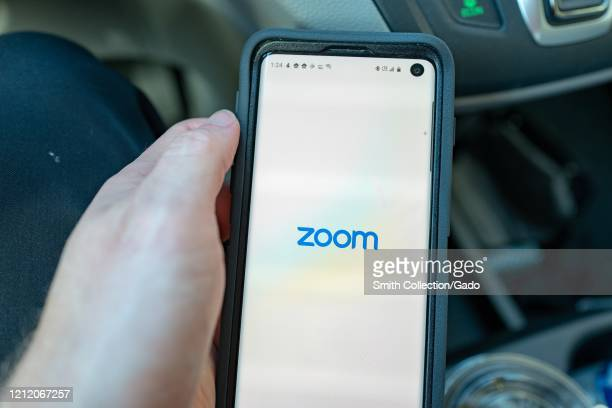 Closeup of hand of a man holding a Samsung Galaxy S10 smartphone with app for teleworking and conference call company Zoom Walnut Creek California...
