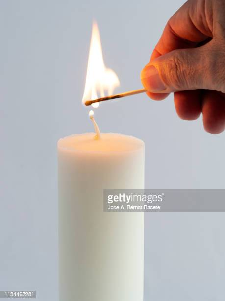 close-up of hand of a man with a match lighting a candle against white background. - candela attrezzatura per illuminazione foto e immagini stock