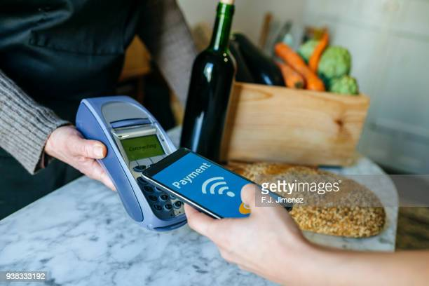 Closeup of hand of person paying in store with mobile phone