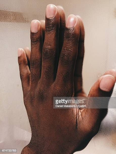 Close-Up Of Hand On Mirror