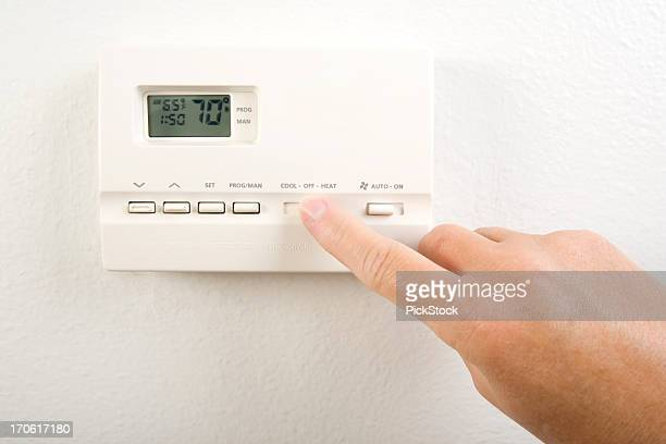 close-up of hand operating the home heating system controls - thermostat stock photos and pictures
