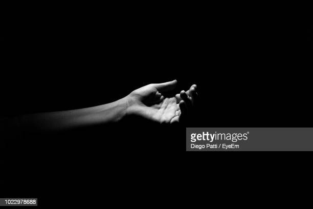 close-up of hand over black background - black and white hands stock pictures, royalty-free photos & images