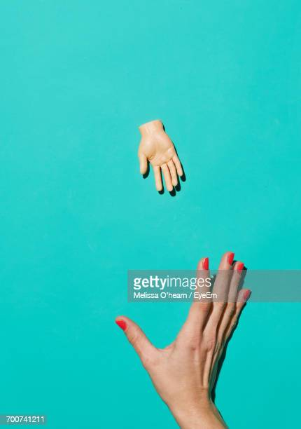 Close-Up Of Hand Over Blue Background