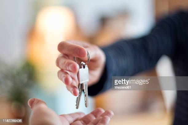 close-up of hand over of house key in new home - 家の鍵 ストックフォトと画像