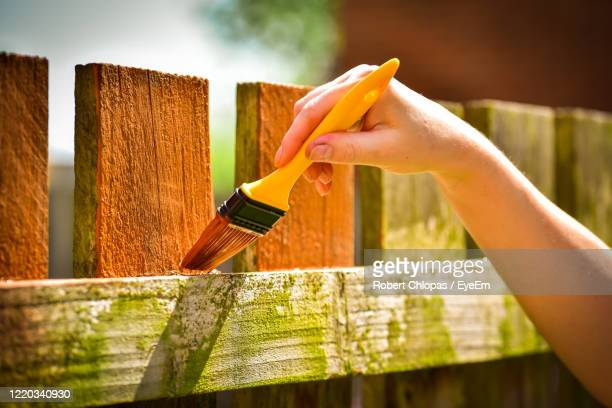 close-up of hand painting wooden fence - fence stock pictures, royalty-free photos & images