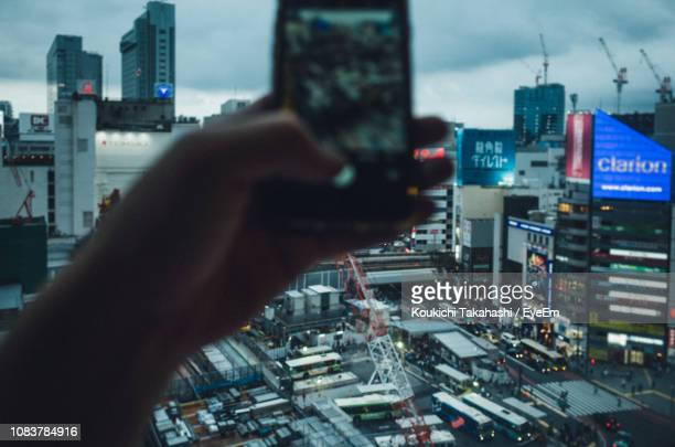 Close-Up Of Hand Photographing Cityscape