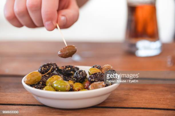 close-up of hand picking olives in bowl on table with toothpick - kalamata olive stock photos and pictures