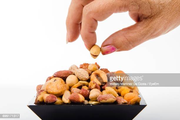 Close-Up Of Hand Picking Up Nut Against White Background