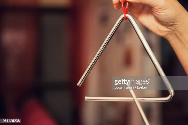close-up of hand playing musical equipment - triangle percussion instrument stock photos and pictures
