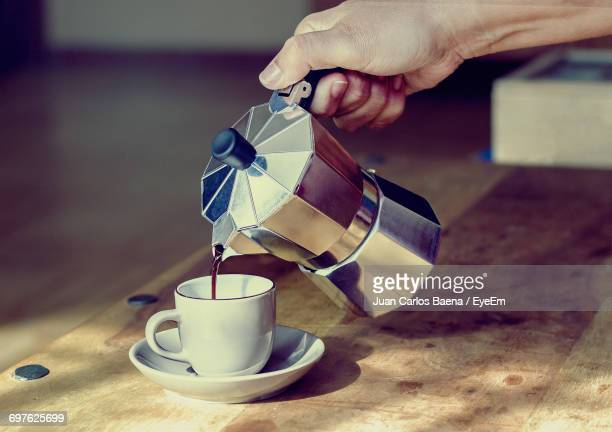 Close-Up Of Hand Pouring Coffee