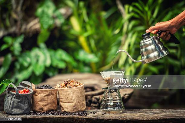 close-up of hand pouring drink on table - civet cat stock pictures, royalty-free photos & images