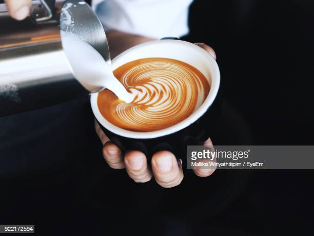 close-up of hand pouring milk in coffee cup - art foto e immagini stock