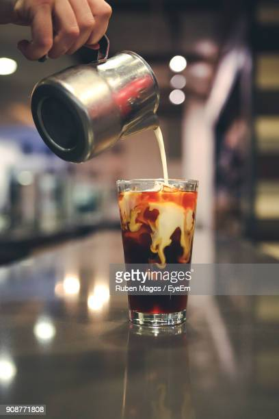 close-up of hand pouring milk in coffee - milk pour stock photos and pictures