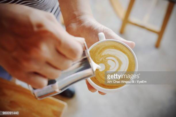 Close-Up Of Hand Pouring Milk In Coffee
