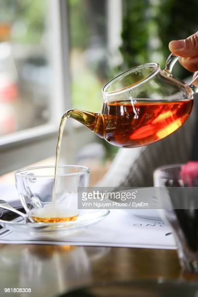 close-up of hand pouring tea in glass - ティーポット ストックフォトと画像
