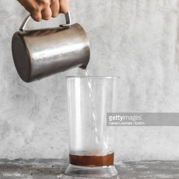 close-up of hand pouring water onto instant coffee in glass - dalgona stock pictures, royalty-free photos & images