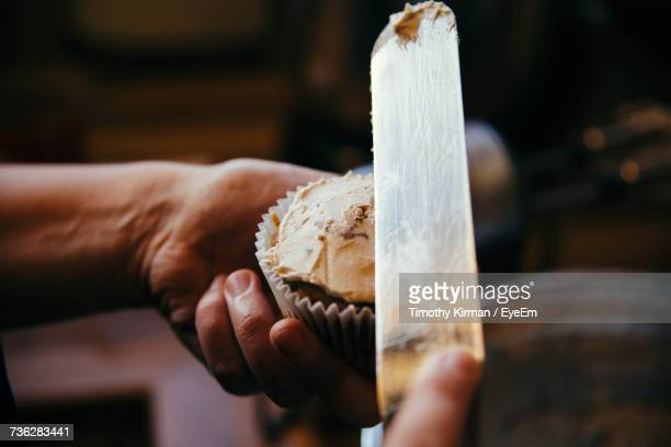 Close-Up Of Hand Putting Icing On Cupcake