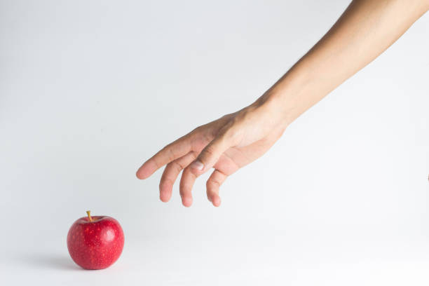 close-up of hand reaching towards apple against white background - hand stock pictures, royalty-free photos & images