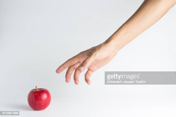 close-up of hand reaching towards apple against white background - reaching stock pictures, royalty-free photos & images