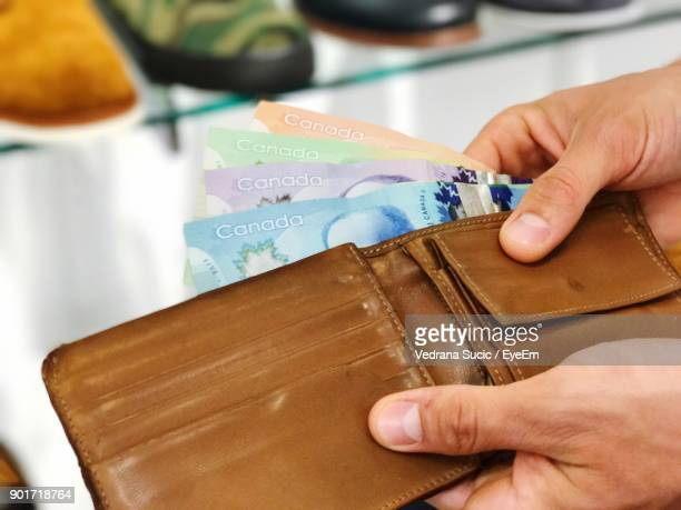 close-up of hand removing money from wallet - canadian currency stock pictures, royalty-free photos & images