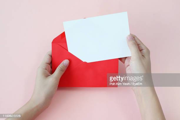 close-up of hand removing paper from envelope over pink background - correspondence stock pictures, royalty-free photos & images