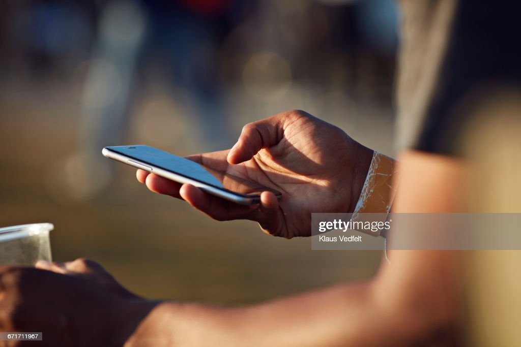 Close-up of hand scrolling on phone at festival : Stock Photo