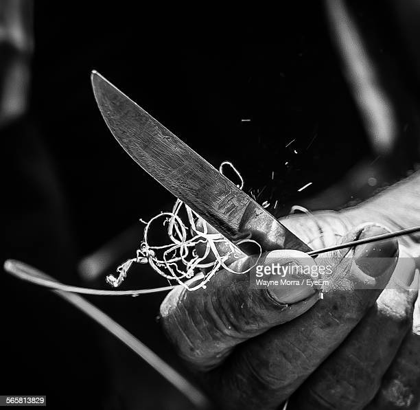 Close-Up Of Hand Sharpening Twig